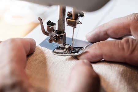 man is having a nasty accident with a sewing machine, sewing needle in his finger Banque d'images