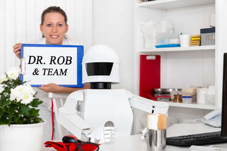 autonomous medical robot in his office with his human team, holding a clipboard with text