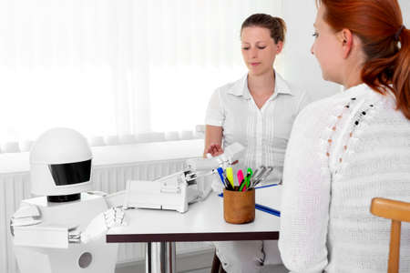 autonomous medical robot is giving a telephone to a female doctor in her office, while sitting behind her desktop