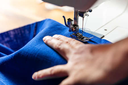 hand of a woman is working with blue linen on a sewing machine
