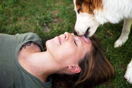 cute puppy dog is licking the face of a pretty young woman, outdoors with green plants in the background