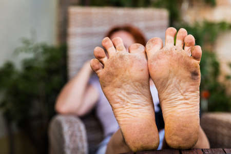 closeup of the bare dirty feet of an adult woman in her garden