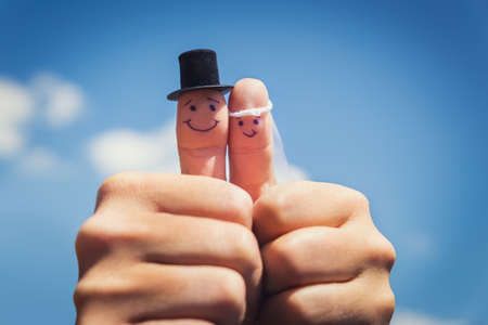 two fingers couple is newlywed in front of a cloudy blue sky Banque d'images