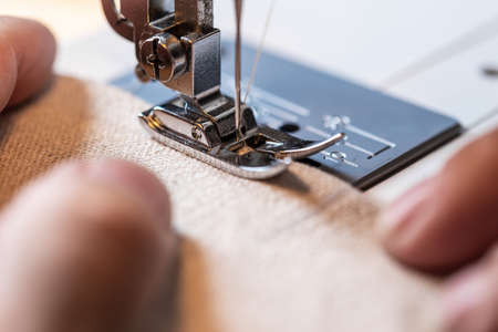 closeup of a woman, working with a sewing machine and beige linen