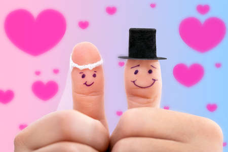two fingers as newlyweds in front of a colorful background with pink hearts, concept wedding invitation and love