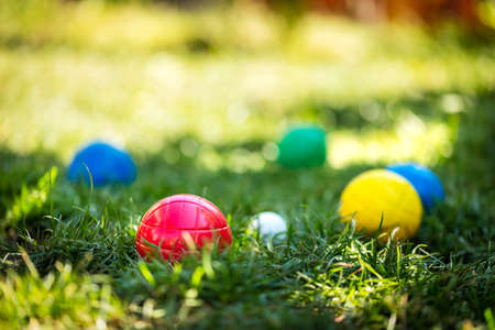 A lot of colorful plastic boules or boccia balls are lying on a green meadow in the summer Banque d'images