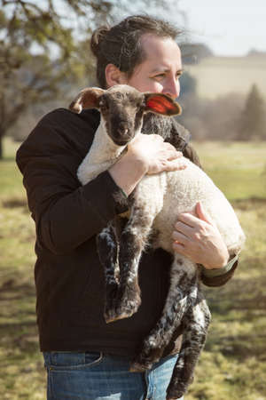 Man holding a cute lamb, concept animal loving and protection