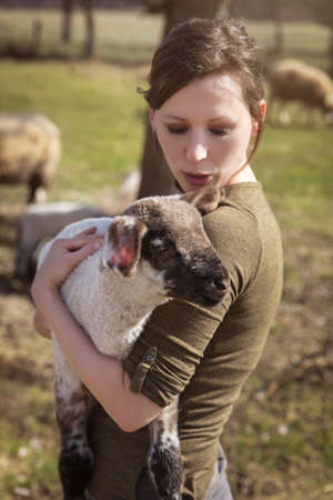 young woman holding a cute lamb, concept affectionate breeding and care