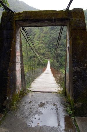 Suspended bridge crossing a tropical river near Las Cascadas, Banos, Equator photo