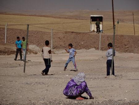 displaced: Children playing, and a guard watching, Gawilah  gawilan  camp, near Bardarash, Kurdistan, Iraq