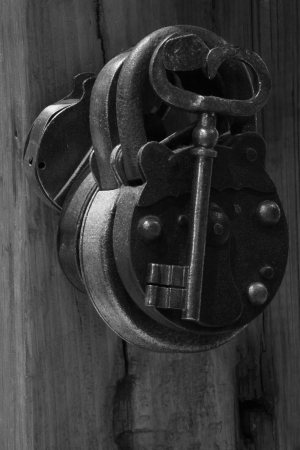 Hanging loop on old metal padlock against the background of timbered wall