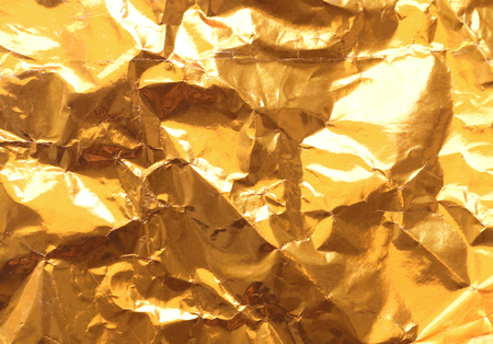 reflectance: Gold Paper creased and folded to provide a textured background