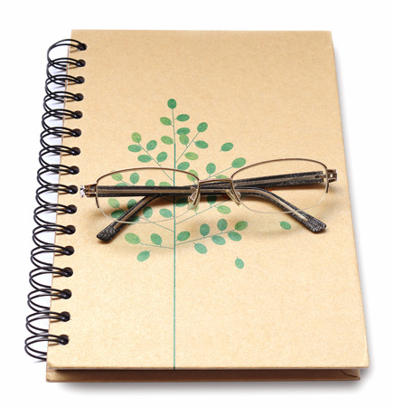 the place is important: Glasses placed on cover notebook, isolated on white background