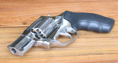 six shooter: Revolver laying on wooden table Stock Photo