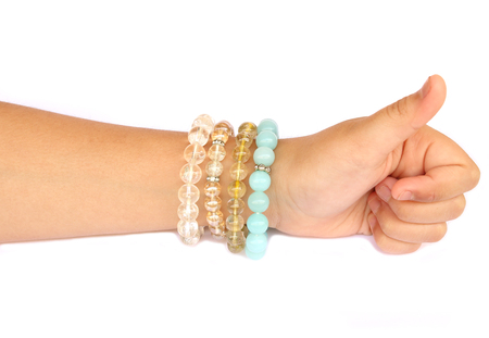 outstretched: Collection of colorful bracelets on woman hand isolated on white background