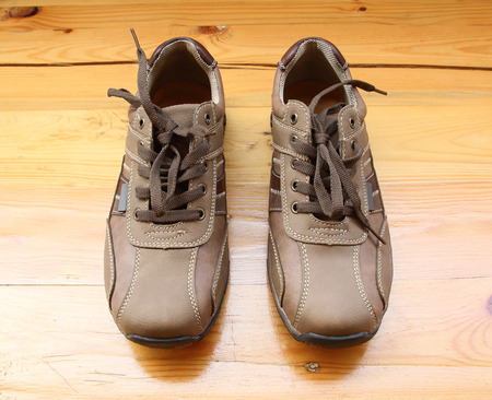 Pair of brown mans shoes on wooden table.
