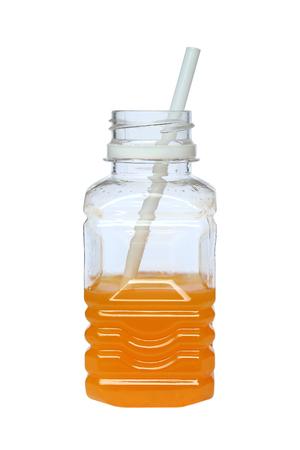 Orange juice in plastic half bottle with a straw on white background Stok Fotoğraf