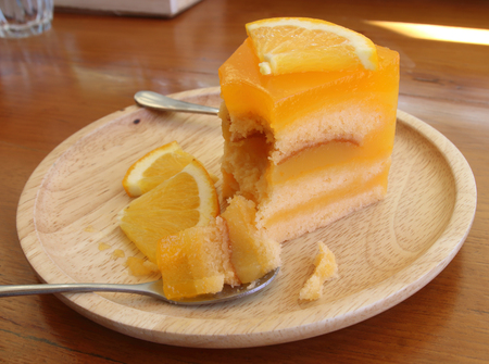 Orange cake with orange slice in wooden dish.