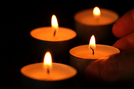 Many candle flames glowing in the dark.