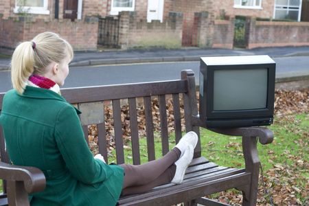 Young girl lying down on a public bench to watch tv photo