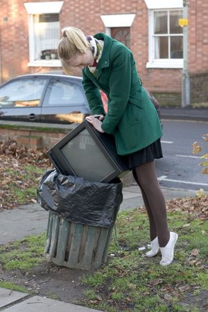 Young girl forcing a tv set into a public bin photo