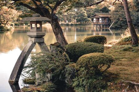 Stone lantern and a lake house in in Kenrokuen garden in Kanazawa Japan Stock fotó