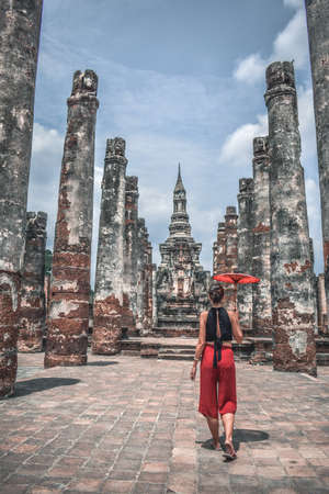 Foreign girl with a red parasol umbrella walking among ancient ruins columns in Suhkotai Thailand