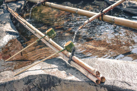 Traditional Japanese ceremonial bamboo ladles used to was hands before entering the temple lying on bamboo sticks Stock fotó