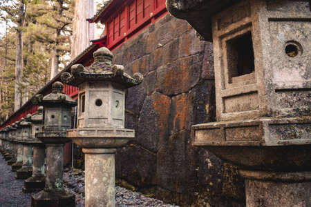Japanese traditional stone lanterns in a row in Nikko Japan