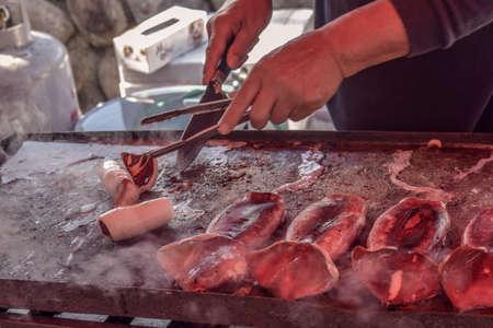 Male hands roasting fresh squid on a street at Miyajima Island in Hiroshima in Japan