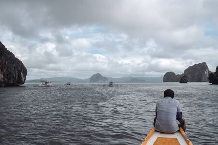 Tourist guide sitting on the nose of a fisherman boat observing boats in rocky sea in El Nido Palawan Island the Philippines