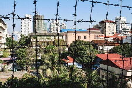 View on Phnom Penh through barbed wire fence from S21 Tuol Sleng Genocide Museum Phnom Penh Cambodia