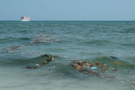 A boat on a polluted sea full of trash in China Asia