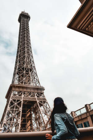 Tourist girl looking up to the copy of the Eiffel Tower at the Parisian Casino in Macau