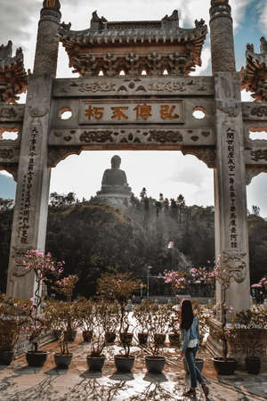 Tourist girl observing the Tian Tan Buddha at the Lantau Island in Hong Kong through traditional Chinese gate Sajtókép
