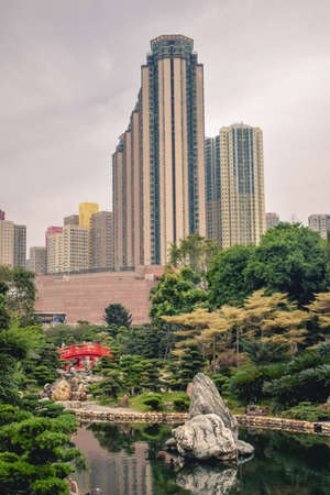 Beautiful contrast between the green trees and blooming flowers and high rise residential buildings in the Nan Lian Garden in Hong Kong China Sajtókép