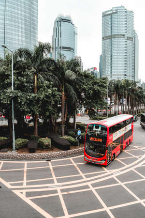 Red double-decker bus passing around palm trees in Hong Kong China