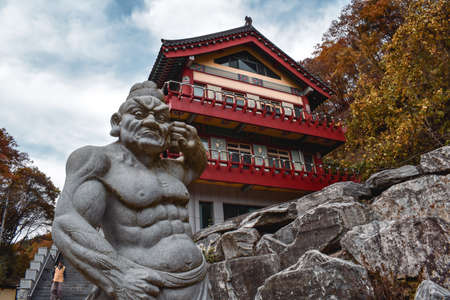Statute of a fighting monk in front of a wooden temple building in Golgusa temple South Korea Sajtókép
