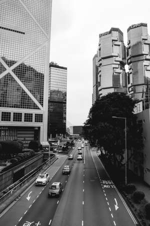 Cars in Hong Kong driving on a calm highway nexto to the Lippo Twin buildings and the Bank of China