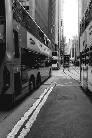 Double-decker trams and busses driving on the streets of Hong Kong China
