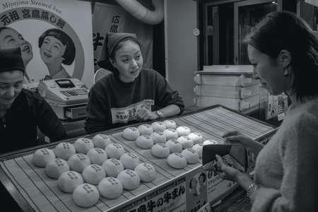 Yong Japanese woman buying street food minced meat buns in Hiroshima Japan