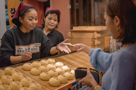 Young woman buying meat buns in Hiroshima Japan