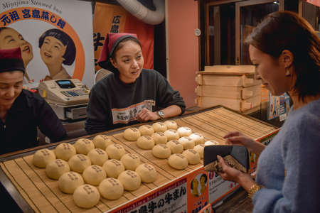 Japanese woman buying street food meat buns in Hiroshima Japan Sajtókép