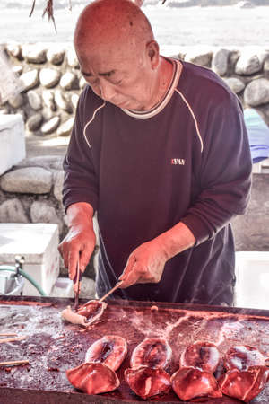 Old Japanese man roasting seafood on the streets in Japan