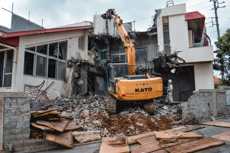 Yellow excavator removing ruins of a house after a typhoon in Naha Okinawa Japan
