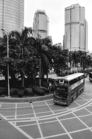 Red double-decker bus turning around palm trees in Hong Kong China