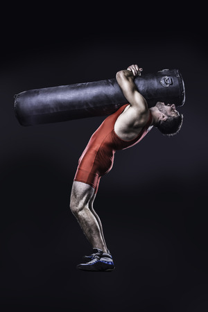 punching bag: young freestyle wrestler in red wrestling uniform perform a throw on punching bag dummy while training