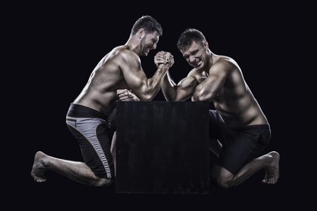 Two muscled young athletes have a hard arm wrestling match on a black box shirtless