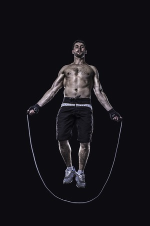 skipping rope: Athlet jumping on skipping rope isolated on black background Stock Photo