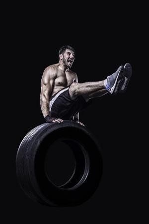 fitness hombres: Equilibrar Atleta en un neumático, manteniendo las piernas rectas aislado en el fondo negro Foto de archivo